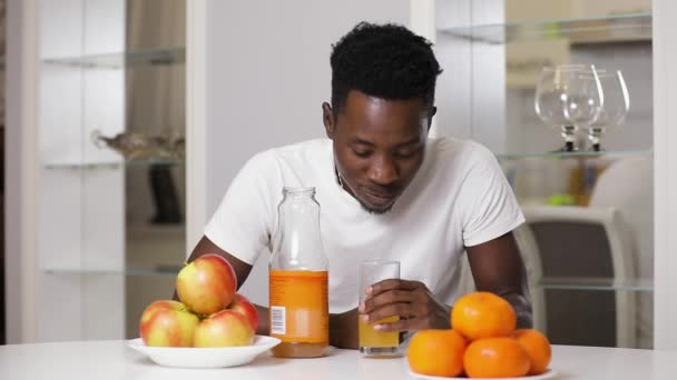 African american man drinking fresh orange or apple juice sitting in white kitchen