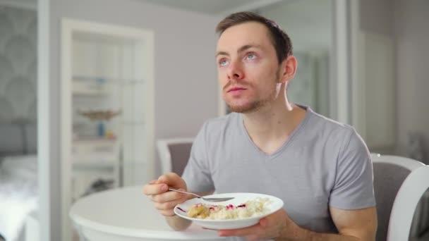 junger Mann isst leckeres Frühstück mit Genuss zu Hause