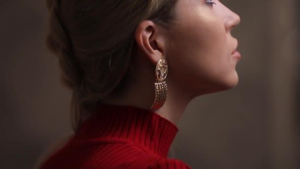 Krásné modelky v červených šatech pózuje s náušnice