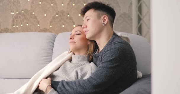 Love, young couple hug on sofa in home