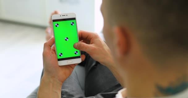 Člověk s použitím webových stránek, prázdné zelená obrazovka smartphone doma