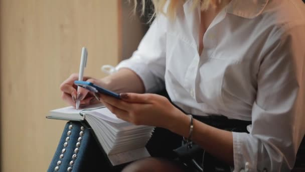 Businesswoman writing in notebook, planning her week