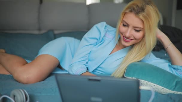 Sexy woman using laptop at home lying on a cozy bed in apartment room in blue pajama, slowmotion