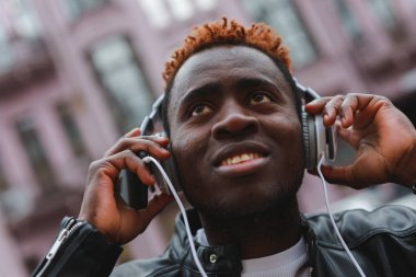 African american man listening to music in headphones at city