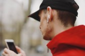 Man listening music in wireless earbud headphones