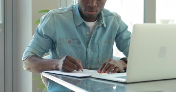 African american businessman write a notes looking at laptop monitor working in office