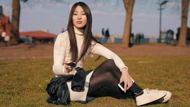 Asian woman sitting in a park with eyewear