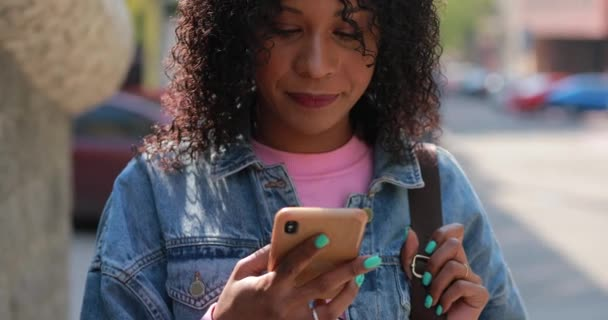 Multiracial woman reading message in phone with laugh in city