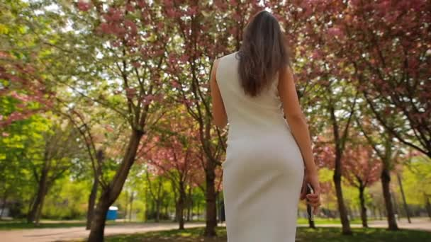Back view of woman looking at blossom trees in summer park touching hair