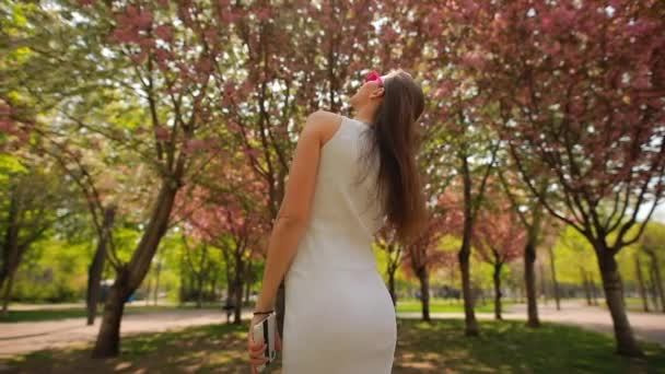 Rear view of woman looking at blossom trees in summer park