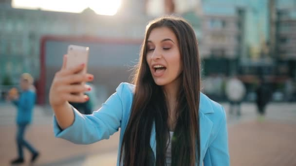 Woman chatting online in city holding smartphone