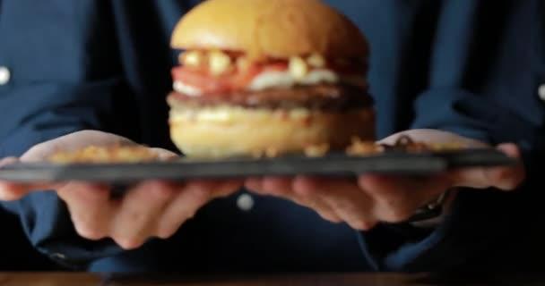 Šéfkuchař podává připravený Burger