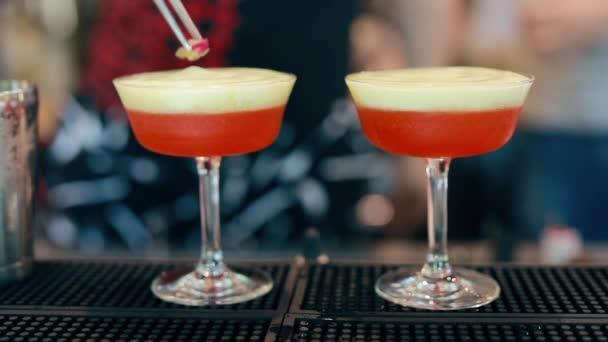 Barmann bereitet Cocktail mit roten Früchten an der Bar zu, fügt Beeren hinzu