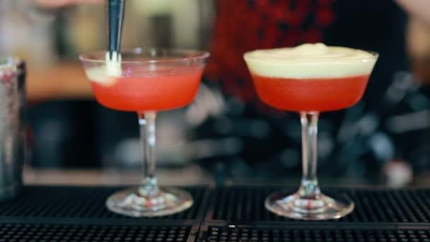 Barmann bereitet Cocktail mit roten Früchten an einer Bar zu