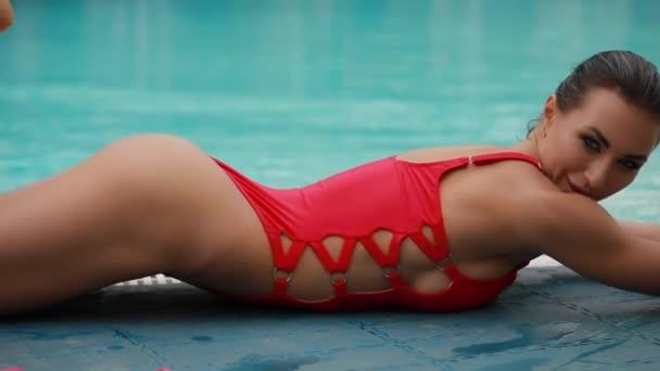 sexy verführerische Frau posiert in rotem Badeanzug in der Nähe von Schwimmbad