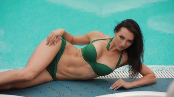 Szexi nő pózol feküdt a medence közelében