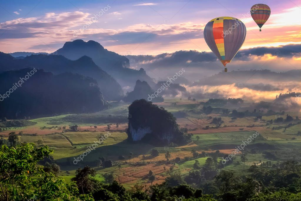 beautiful scenary in the north part of Thailand over the valley of mountain at sun rising beautiful color on the mist in the field hot air balloon flying in sky (selective focus and white balance shifting applied)