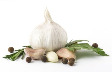Fresh garlic with black pepper grains and green leaves on white background