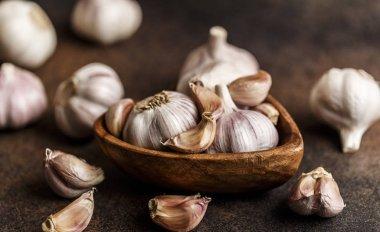 Garlic bulbs with garlic cloves in wooden bowl on dark background