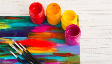 Colorful acrylic paints with paint brushes on colorful artwork