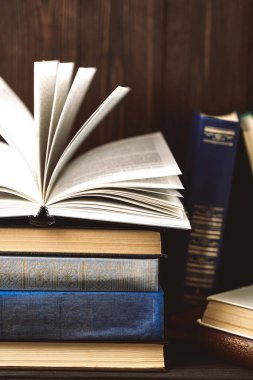 Old open book on stack on vintage books on wooden background