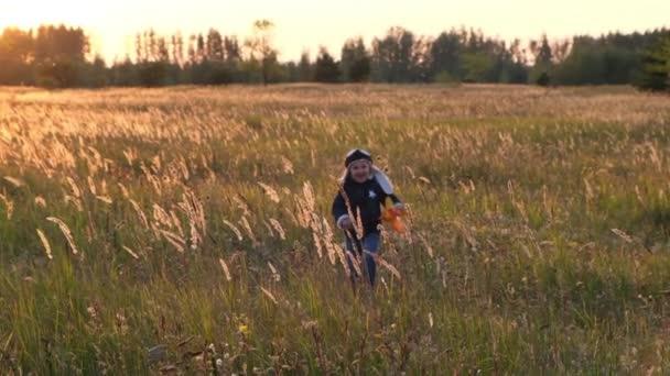 Boldog gyerek játszik a játék repülőgép ősz felé ég a háttérben naplementekor. Boldog gyermekkorban. Lassított mozgás