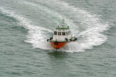 PENANG, MALAYSIA - January 02, 2017: Orange and white pilot boat arrives to collect pilot from ship at Malacca Strait water near George Town.