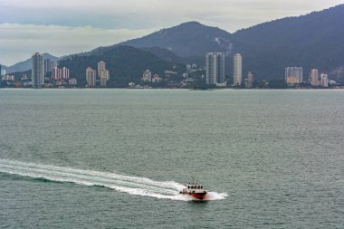 PENANG, MALAYSIA - January 02, 2017: Orange and white pilot boat arrives to collect pilot from ship at Malacca Strait water next to George Town on the opposite shore.