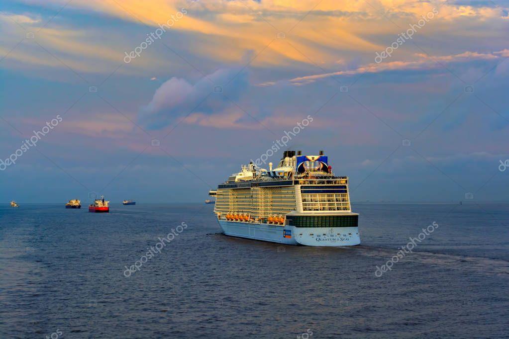 SHANGHAI, CHINA - May 12, 2017: Quantum-Class giant cruise passenger ship 'Quantum of the Seas' by Royal Caribbean International (RCI) sails at sunset twilight near Shanghai.