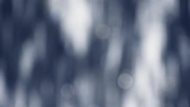 Abstract blur background of colorful blue bokeh glitter of defocused water ripples, fast running vertically, close up, slow motion