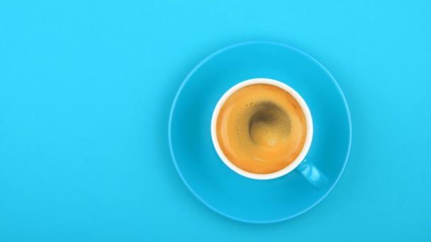 Közelről egy teljes fehér csésze eszpresszó kávét és csészealj pasztell kék háttérben kávé bevezetésekor, emelt szintű felülnézet, spin animált lassított át közvetlenül felett