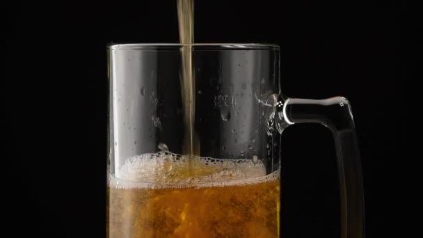 Nahaufnahme Hintergrund von einschenkendem Lagerbier mit Blasen und Schaum im Glaskrug über schwarzem Hintergrund, Überfüllung und Auslauf, nach oben fließend, Seitenansicht niedrig, Zeitlupe