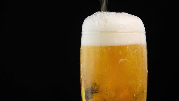 Zblízka pozadí nalévání piva ležák s bublinami a pěna ve skle nad černým pozadím, přeplnění a dojdou, teče přes vrchol, nízký úhel boční pohled, zpomalené