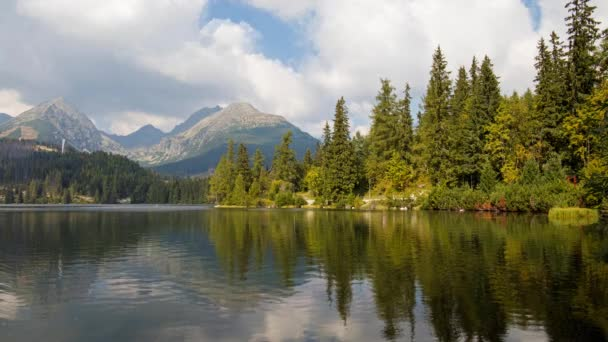 Animated cinemagraph of cloudy sky over green summer forest and rippled water of mountain lake