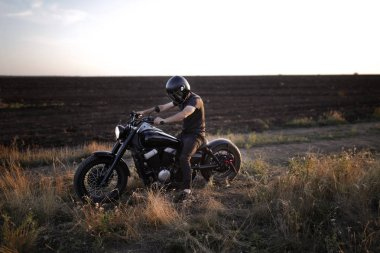 Racer  in the black helmet sitting on the motorcycle, on the field, alone, nobody else, sun set, free, strong, riding, extreme, sport, travelling