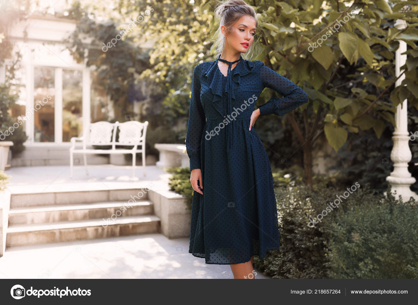 Posing professional model in the back yard of the restaurant, wearing the green dress, hand on the waist, garden, outdoor, makeup, hair bun, ...