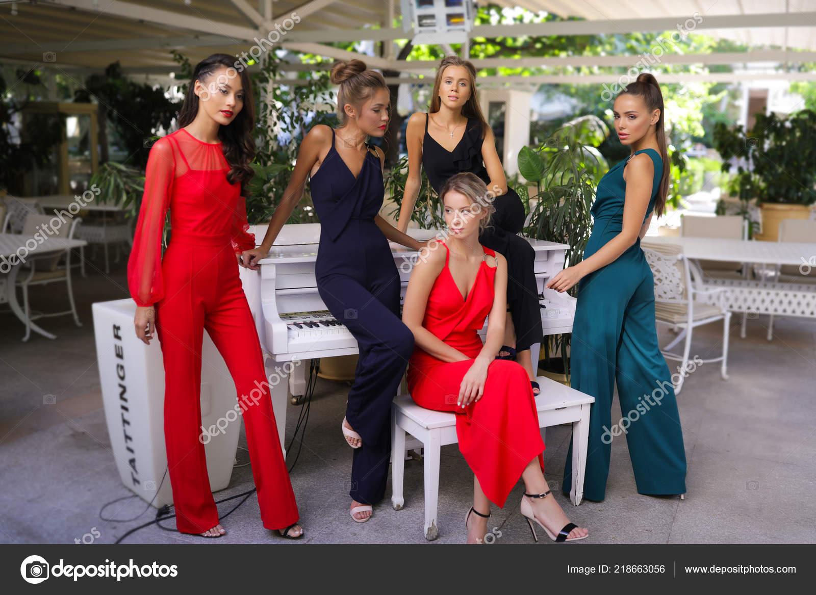8e1049787100 Καταπληκτικό Πέντε Κορίτσια Στα Διαφορετικά Πολύχρωμα Κοστούμια Στέκεται Κοντά  Πιάνο– εικόνα αρχείου