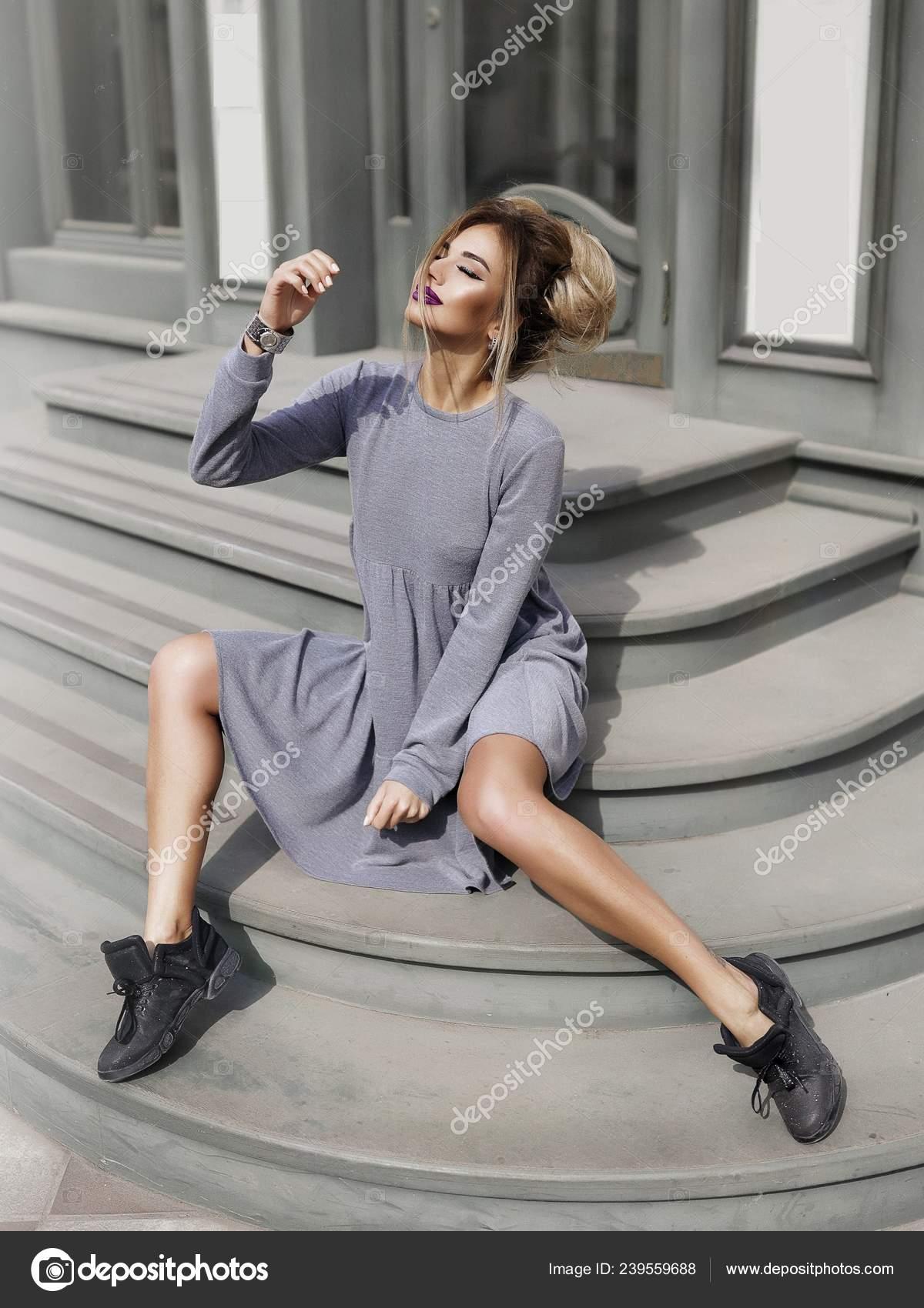 e5d7e5d7e48 회색 드레스와 블랙 스 니 커 즈 야외 카페 근처 계단에 앉아 멋진 젊은 모델. 머리, 예쁜 얼굴, 세련 된 헤어스타일에 메이크업.  부드러운 부드러운 피부, 슬림 바디.