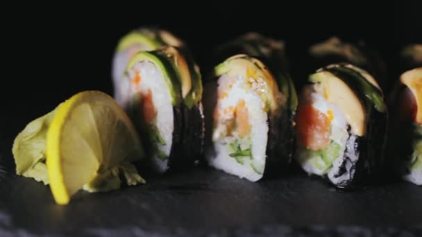 Sushi s plátky lososa a čerstvé okurky. Chutné sushi na černou kamennou desku. Detail