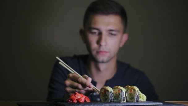 Young man eating sushi with chopsticks
