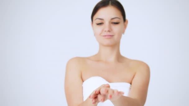 Mladá žena použití rukou hydratační krém, dobře upravené ruce, péče o pleť na bílém pozadí