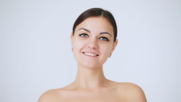 Közelkép portréja gyönyörű nő keres kamera vonzó mosollyal. Szépség és a bőr care koncepciót.