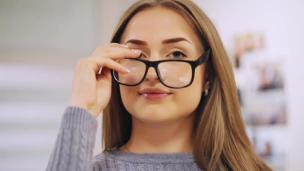 Detail portrétu krásná žena úsměvy pro fotoaparát, klade na brýle