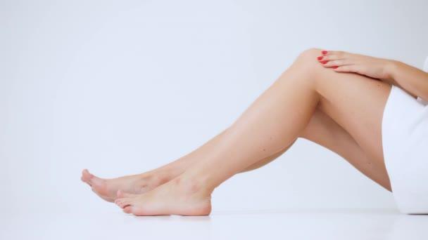 Detail nohy mladá žena, dívka masáže bolavé koleno, háčky a smetany, sit izolovaných na bílém pozadí