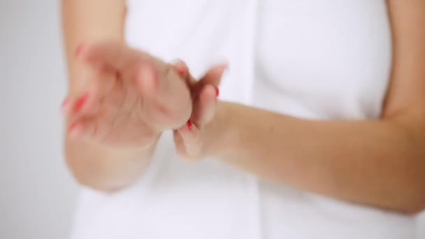 Young woman applying hand moisturizing cream, girl in towel rubs her hands, skin care on a white background