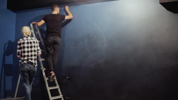 Graffiti umělci kreslí obrys na modré zdi. Muž na schodech připravuje na zeď pro kreslení