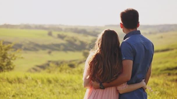 junges Paar, das in der Natur am Sonnenuntergang steht und irgendwo in der Ferne darauf zeigt