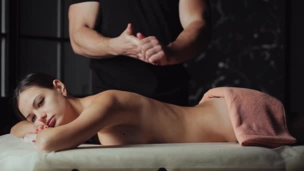 Svalnatý muž masér připravit, dělá masáž zad. Krásná mladá žena ležící na masážní stůl