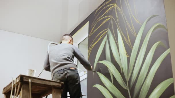 Man makes art wall painting. Graffiti artist drawing with paint on wall. Art Concept.