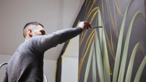 Graffiti umělec kreslení s barvou na zdi. Mužské ruky s kartáčem